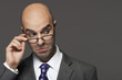 Balding businessman hand on glasses, making a face