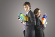 Smiling businesspeople standing back to back, holding water guns, side view