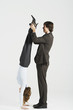Young businessman holding legs of female colleague standing on hands, profile