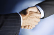 Middle-aged businessmen shaking hands, close-up, digitally enhanced