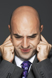 Bald businessman with fingers in ears, making a face