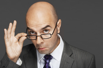 Balding man hand on glasses, making a face