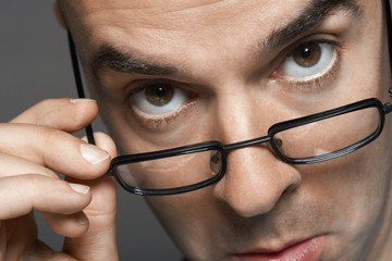 Balding man hand on glasses, making a face, close-up