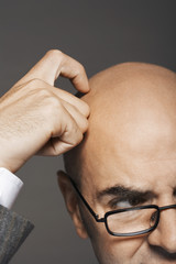 Bald businessman wearing glasses, scratching head, high section