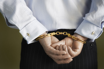Businessman standing with hands handcuffed behind back, mid section, back view