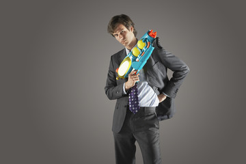 Businessman standing, holding water gun, hand on hip