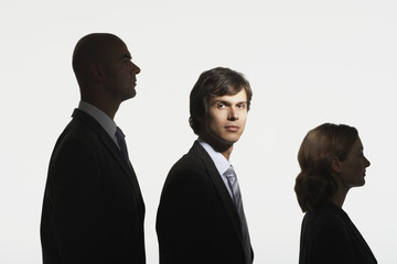 Businesspeople standing in row, in height order, middle man facing camera in spotlight
