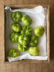Green tomatoes in wooden box, overhead view