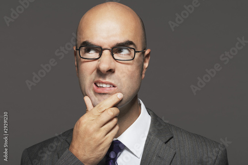 Bald businessman wearing glasses with hand on chin, making funny face