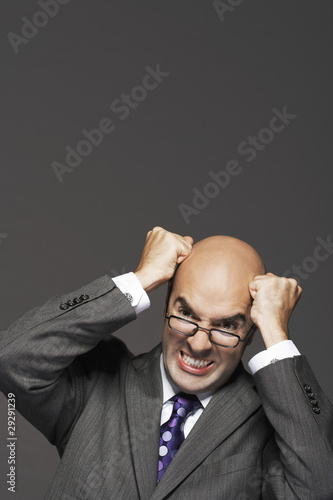 Bald businessman, fists on head, pounding head, making a face