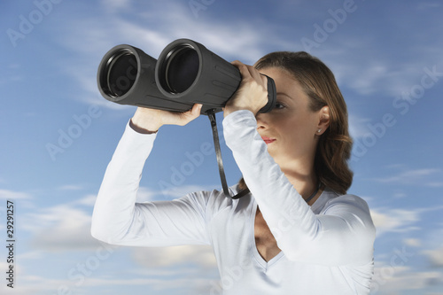 Mid-adult woman standing outside, looking through large pair of binoculars