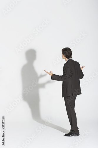 Young businessman standing, arguing with own shadow