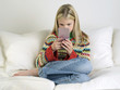 Girl sitting, barefoot on sofa, Playing Handheld Video Game