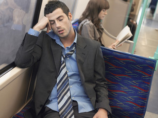 Businessman with loosened tie, sleeping on Commuter Train