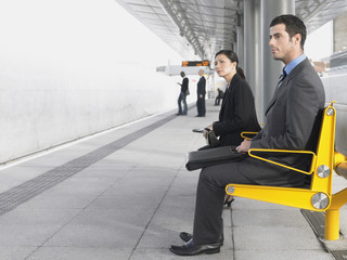 Businesspeople sitting on benches, Waiting at Train Station, side view