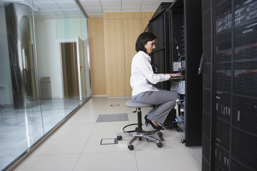Female technician working in server room
