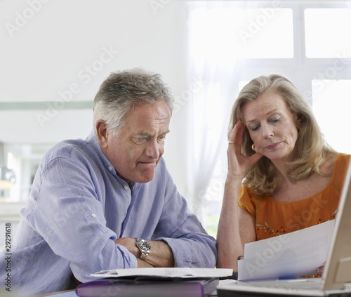 Senior couple looking at bills, sitting at dining table