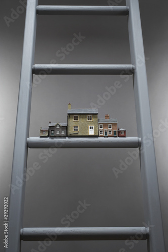 Small model houses on ladder