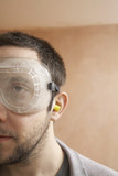 Man wearing protective eye goggles and earplugs indoor, close up