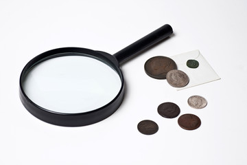 Old Coins and Magnifying Glass