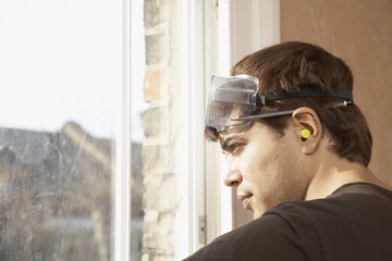 Man wearing goggles and earplugs, looking out window