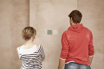 Couple choosing sample paint colours on wall, back view