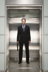 Businessman standing in open Elevator, portrait, front view