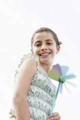 Smiling pre-teen girl holding pinwheel, low angle view