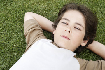 Pre-teen boy lying on back in grass, hands behind head, elevated view