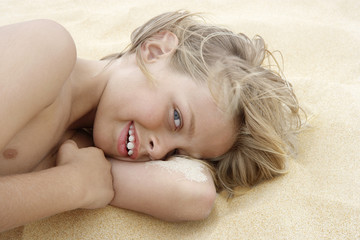 Pre-teen boy lying on arm in sand, close-up
