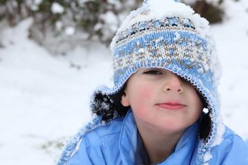 bambino con cappello pieno di neve