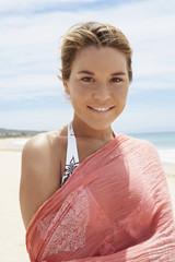 Young woman in bikini and shawl standing on beach
