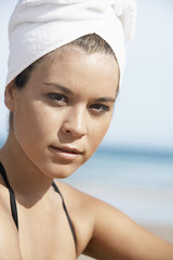 Young woman with hair wrapped in towel on beach, close-up