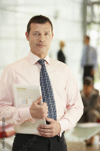 Businessman Holding Report in office, portrait