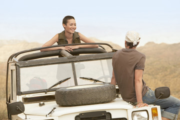 Young couple sitting in stationary four wheel drive vehicle in desert