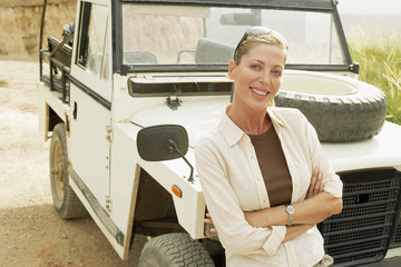 Woman standing in front of four wheel drive car in desert, portrait