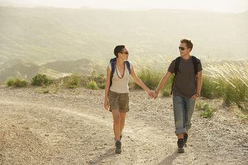 Couple of hikers holding hands, walking on country road