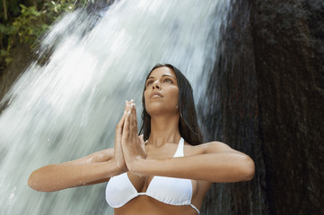 Young woman meditating by waterfall, low angle view