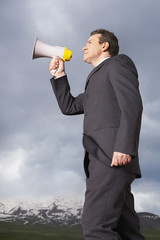 Businessman in mountain field Speaking Through Megaphone, low angle view