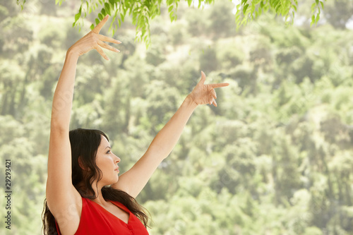 Woman dancing outdoors, side view.