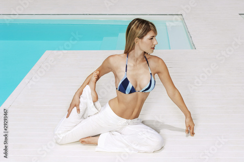 Young woman stretching legs by swimming pool, front view, full length
