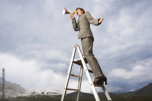 Businesswoman on ladder in mountain field shouting Through Megaphone, low angle view