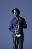Trombone Player standing with hat, smiling
