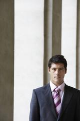 Businessman standing by pillars outside building, portrait
