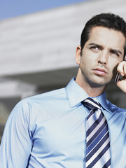 Businessman standing in plaza using cell phone