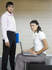 Male and female office workers standing in lobby, portrait