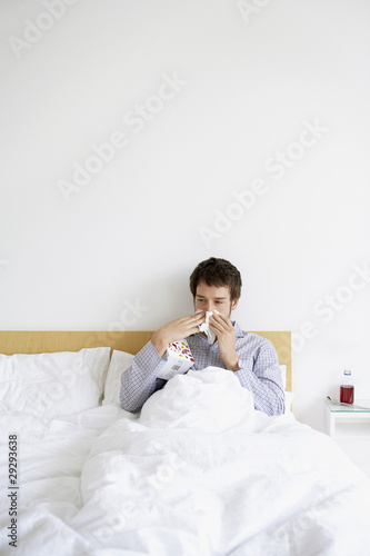 Man with cold in bed blowing nose
