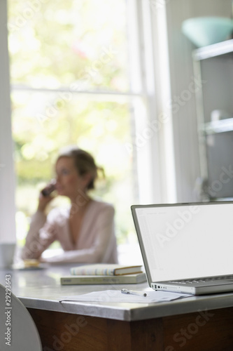 Woman on phone sitting at kitchen table by laptop, focus on laptop