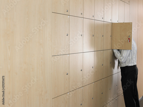 Businessman putting head in small locker