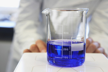 Scientific glass container with blue liquid, technician in background